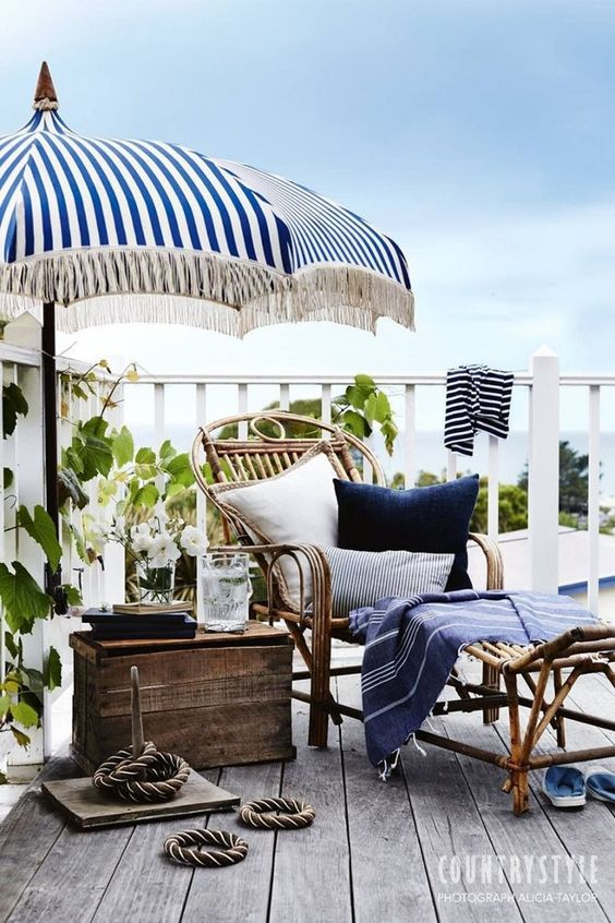 a seaside terrace with a wooden deck, rattan and wooden furniture, bright blue textiles, rope and some greenery