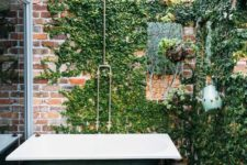 a shabby chic bathroom with brick walls done with climbing greenery and a green bathtub