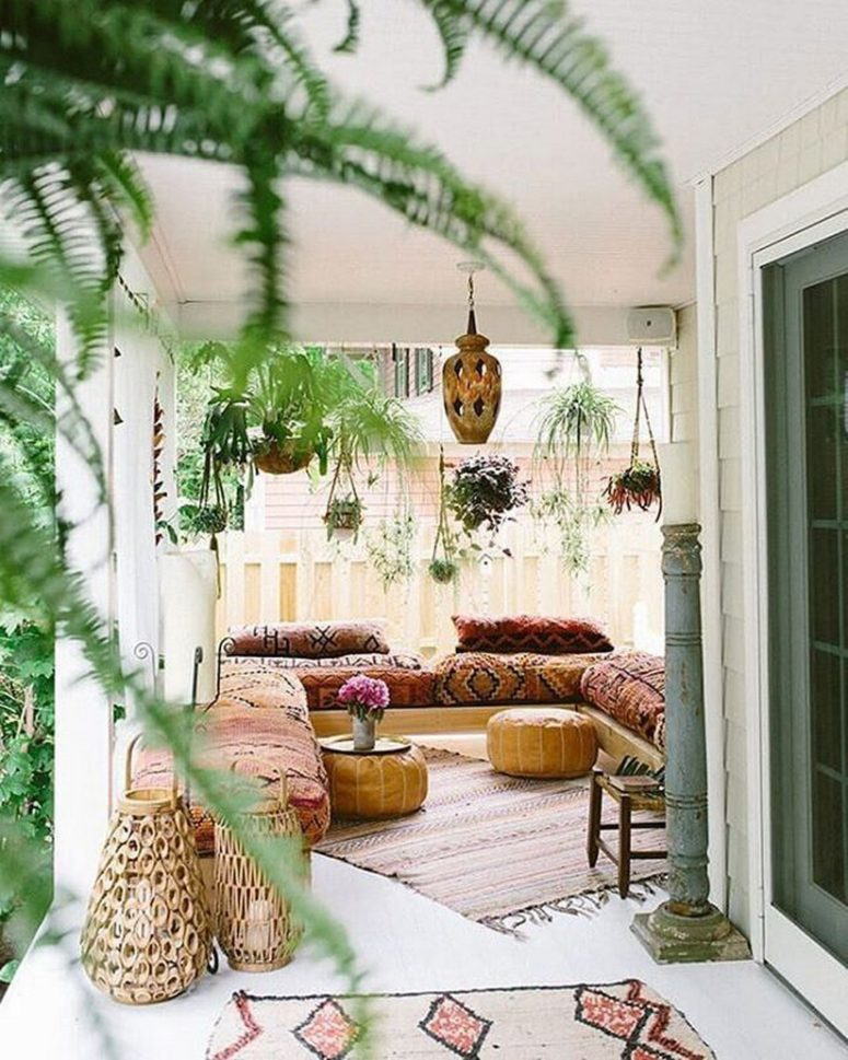 a simple Moroccan space with hanging potted greenery, boho rugs, boho textiles and rattan lanterns