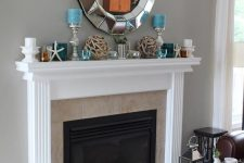 a simple and stylish beach mantel with driftwood balls, blue and white candles, glass candleholders and starfish