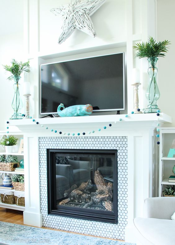 a simple beach mantel with a blue pompom garland, a turquoise whale figurine, aqua vases with greenery and a whitewashed driftwood star