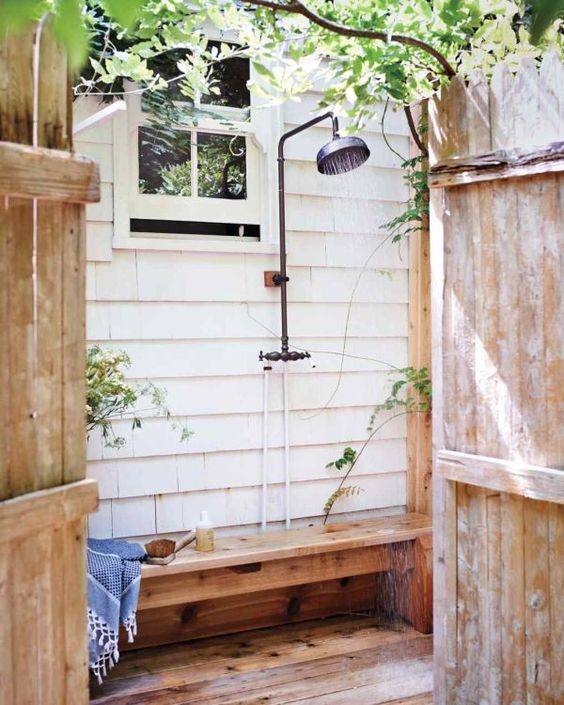 a simple outdoor shower with a wooden bench and some greenery around