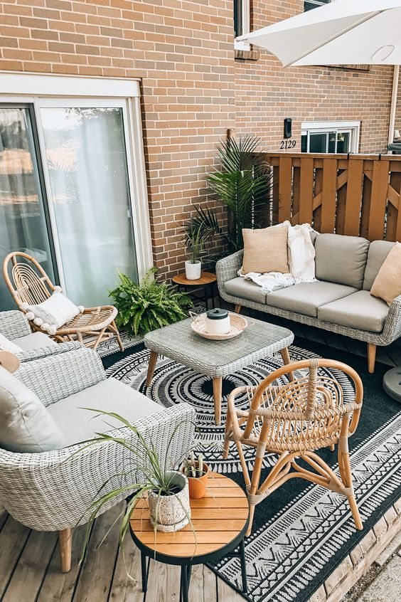 a small beach terrace with neutral wicker furniture, rattan chairs, potted plants and a bold boho rug