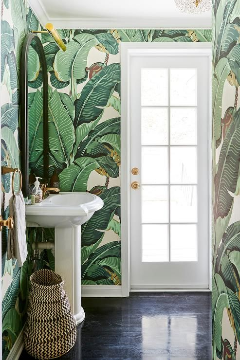 a small tropical powder room with banana leaf wallpaper, a free-standing sink, a basket and gold touches