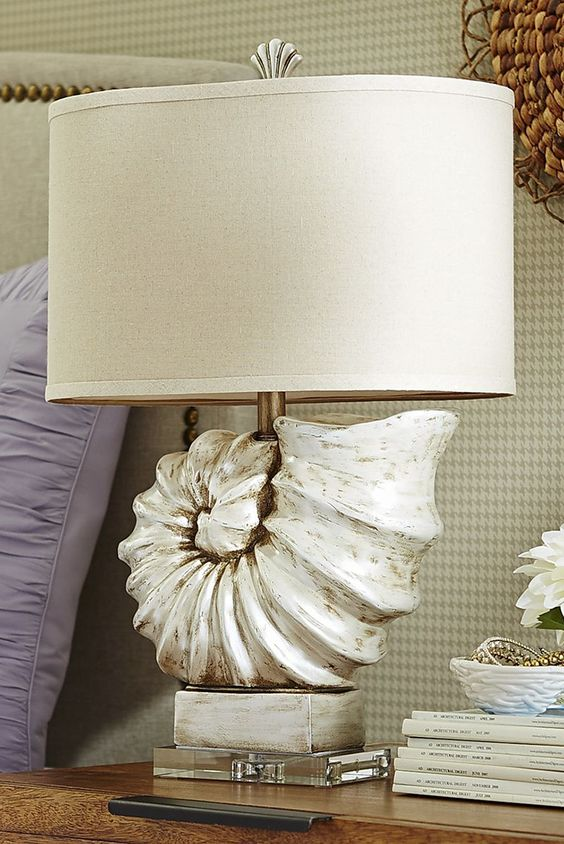 a statement table lamp featuring an oversized seashell and a plain lampshade is a gorgeous idea for any beachy space