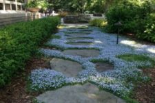 a stone garden path with white blooms and greenery in between looks very chic and very inspiring