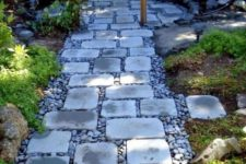 a stylish and comfrotable garden path of pebbles and simple stones contrasts the greenery around