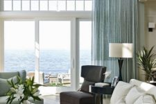 a stylish beahc living room with an aqua curtain, aqua furniture, a dark chair and a creamy sofa
