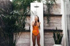 a stylish modern outdoor shower with weathered wood, pebbles, potted plants and a shower