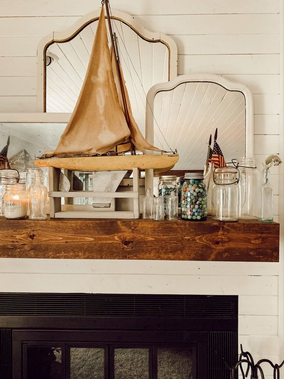a summer beach mantel with jars, mini shells in a jar, a large boat, a candle in a jar and several mirrors