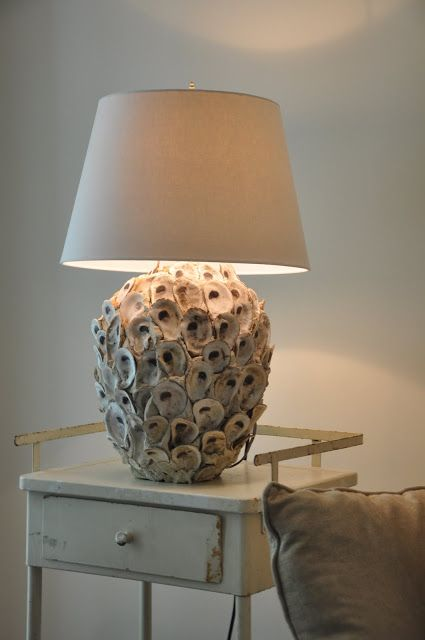 a table lamp with a base covered with seashells and a plain lampshade is a lovely idea for a seaside or beachy space