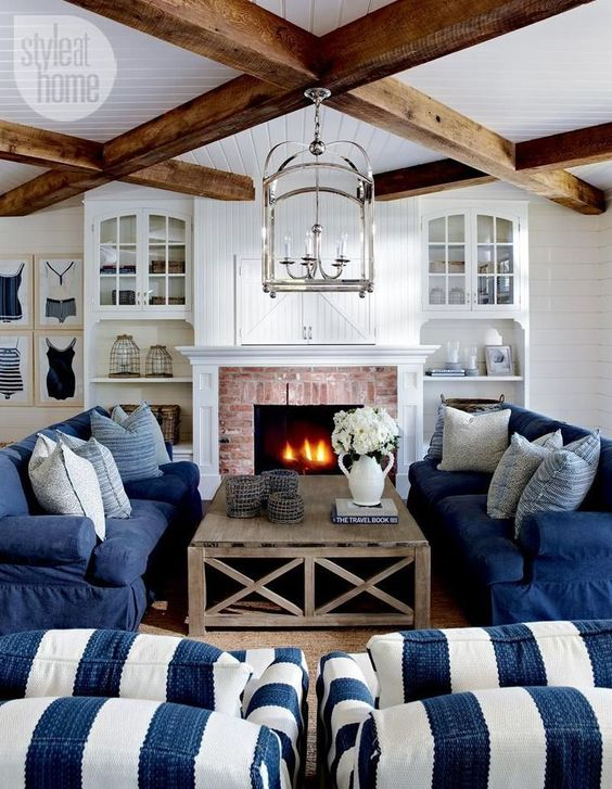 a traditional coastal living room in navy and white, with stripes, a brick clad fireplace, wooden beams and built-in shelves