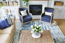 a traditional coastal living room with a tan and navy color scheme, rattan, leather and a mantel with greenery
