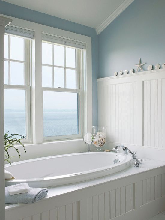 a traditional sea-inspired bathroom done in white and blue, with an oval sunken tub and a gorgeous view to the sea