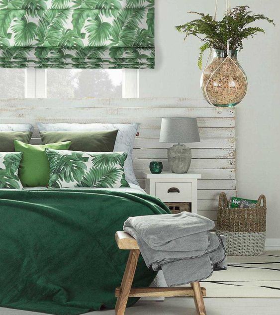 a tropical Roman shade and bedding, a basket and a potted plant brign a tropical feel to this neutral sleeping space