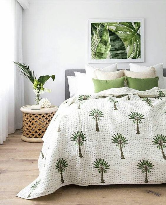 a tropical artwork, bedding and a carved wooden nightstand create a mood and a feeling in this tropical space