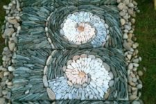 a unique garden pathway with neutral pebbles and tiles covered with grey, blue and white pebbles that are designed in swirls