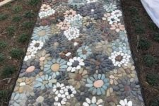a very eye-catchy pebble garden pathway with muted pebbles and floral patterns all over is a real masterpiece