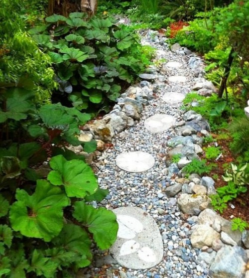 a very wild-looking garden path done with pebbles, large rocks and round tiles printed with leaves