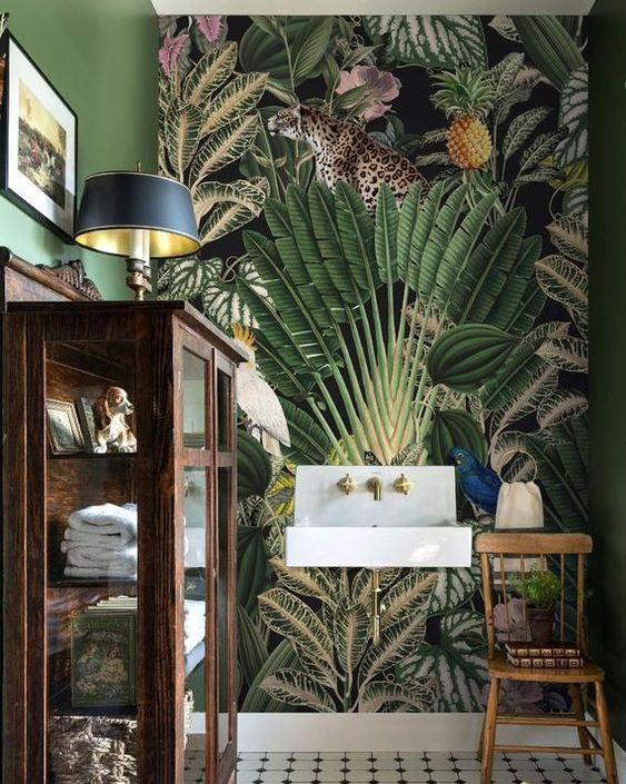 a vintage tropical bathroom with a catchy mural wall, a vintage glass armoire for storage and gold accents