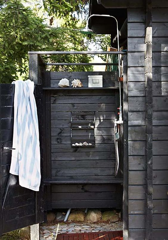 a weathered wood outdoor shower with shelves, sea-inspired decor and stones on the ground