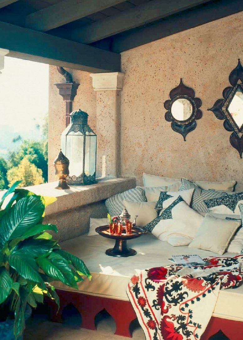 a welcoming Moroccan patio with a carved daybed, a vintage mirror, metal lanterns and a tray with drinks