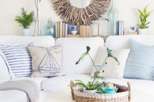 a welcoming beach living room with a white sofa, a basket for accessories and a driftwood mirror
