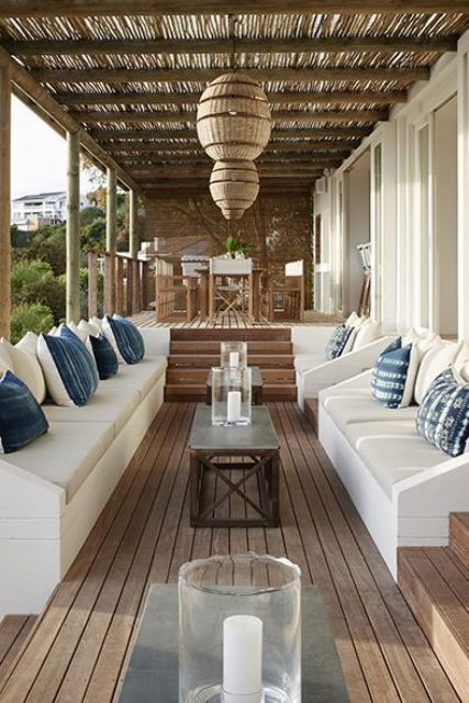 a welcoming beach patio with white benches, blue pillows, pendant wicker lamps and a dining set of wood