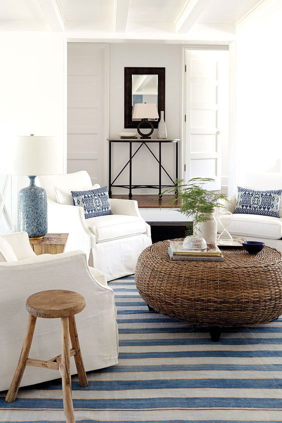 a welcoming coastal living room with a rattan ottoman, a striped rug, white furniture and blue lamps and pillows