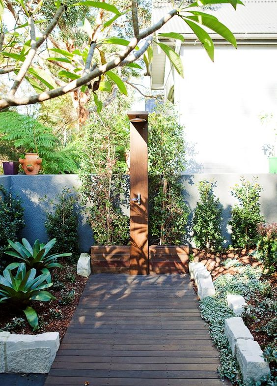 a welcoming outdoor shower done with wood, rocks and planted greenery all around