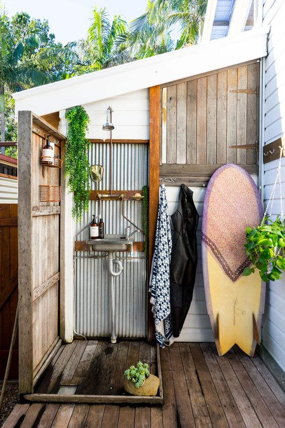 a welcoming outdoor shower with corrugated steel, weathered wood and a surf board