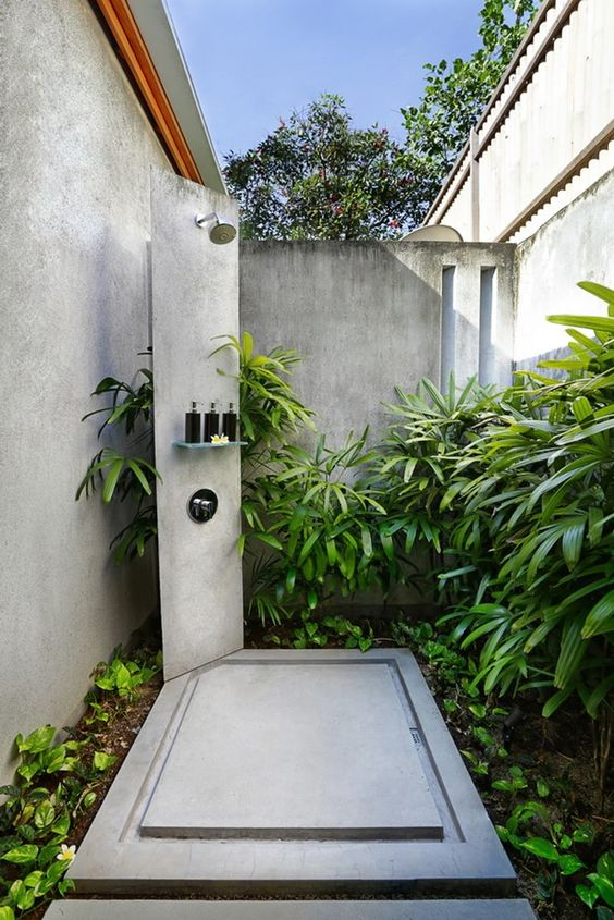 a welcoming outdoor shower with much greenery and a concrete shower zone with a stand