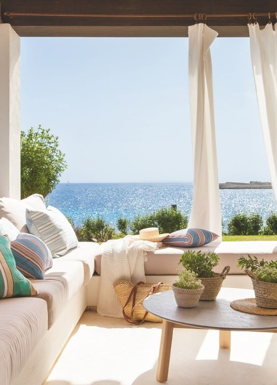 a welcoming seaside patio with a corner bench, potted greenery, baskets, colorful pillows and a fantastic view