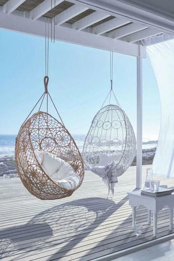 a white beach deck with a vintage stool, pendant wicker chairs and white textiles seems ethereal and chic