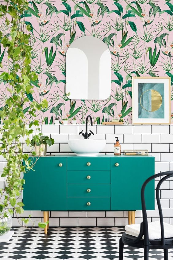 an airy and fun tropical bathroom with catchy wallpaper, a green vanity, cascading greenery and touches of gold
