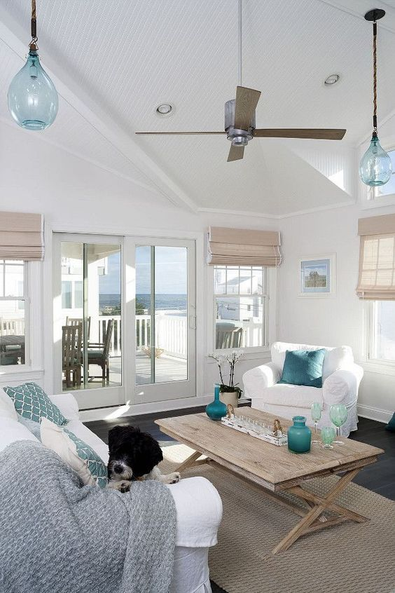 an airy beach living room with woven Roman shades, a wooden table, touches of blue and turquoise, white upholstered furniture