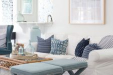 an airy ocean-inspired living room with light blues and navy, printed pillows, light blue stools, artworks and a rattan table