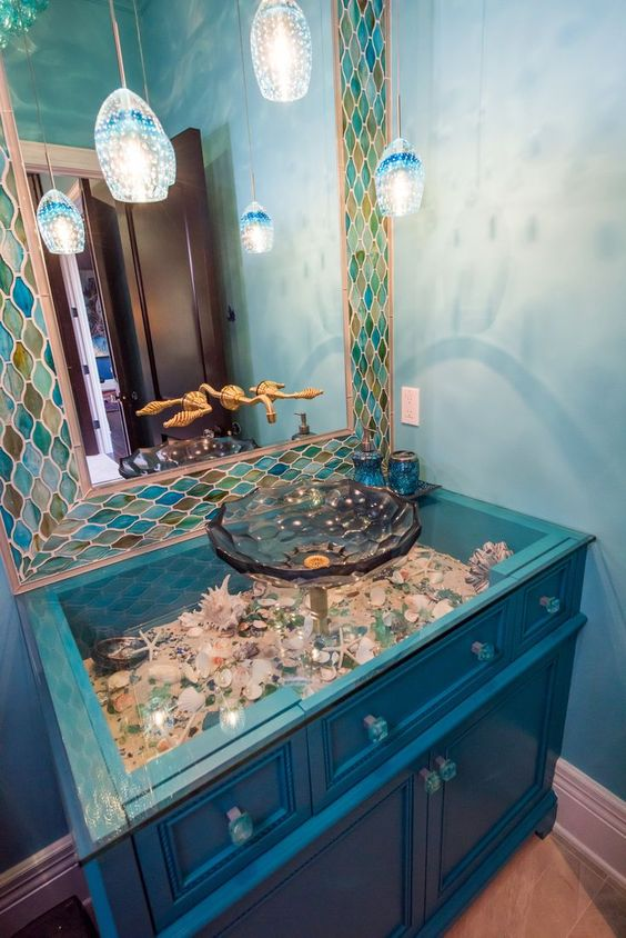 an electric blue vanity with a glass tabletop and seashells and pebbles under it plus jellyfish inspired pendant lamps