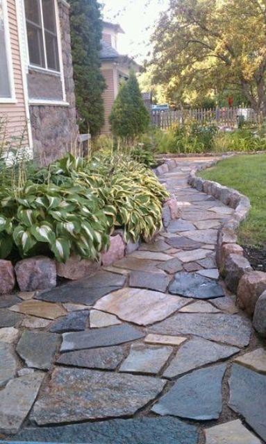an elegant rough stone garden path with a high border looks stylish and very textural