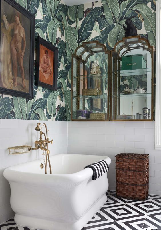 an elegant vintage tropical bathroom with banana leaf wallpaper, a catchy tub, glass and mirror cabinets and artworks