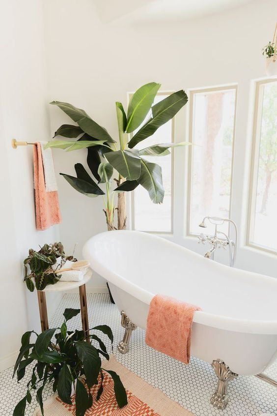 an ethereal tropical bathroom with a vintage clawfoot tub, potted greenery and peachy pink textiles
