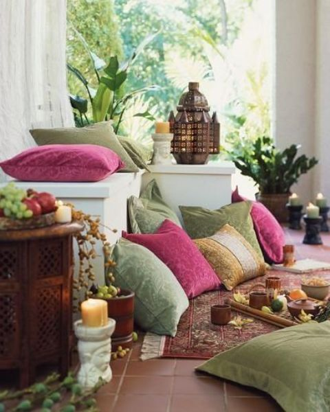 an exotic Moroccan patio done in green and pink, with potted greenery, lanterns and candle lanterns