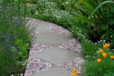 an eye-catchy garden path done with large grey tiles and red, blue and white pebbles around them