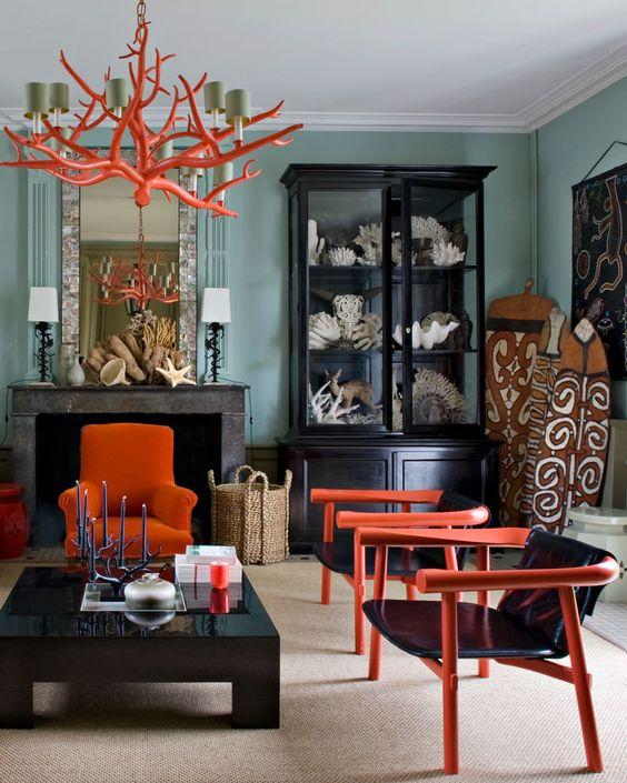 an orange coral-inspired chandelier that echoes with the chairs in the room helps it feel like the sea