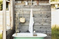 an outdoor rustic bathroom nook with weathered wood screens, a green tub, a pallet rug and some accessories