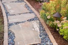 an unusual garden path made of pebbles and rough stones plus a matching border feels accurate though not too much