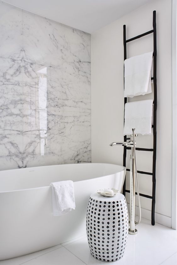 monochromatic chic with a white marble wall, an oval tub, a black ladder and a printed side table