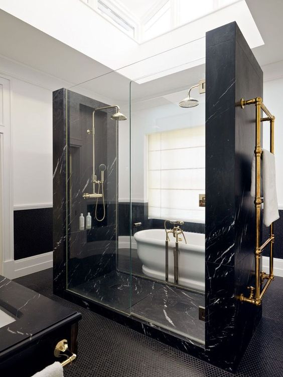pure elegance and drama in this bathroom done with black marble, blakc penny tiles and a white vintage tub