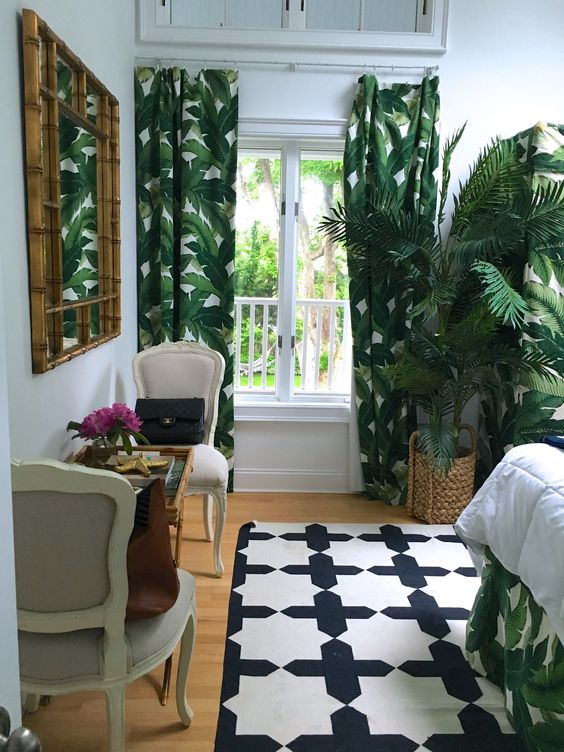 tropical print curtains and bedding, a potted palm, a bamboo mirror help to create an ambience in the bedroom