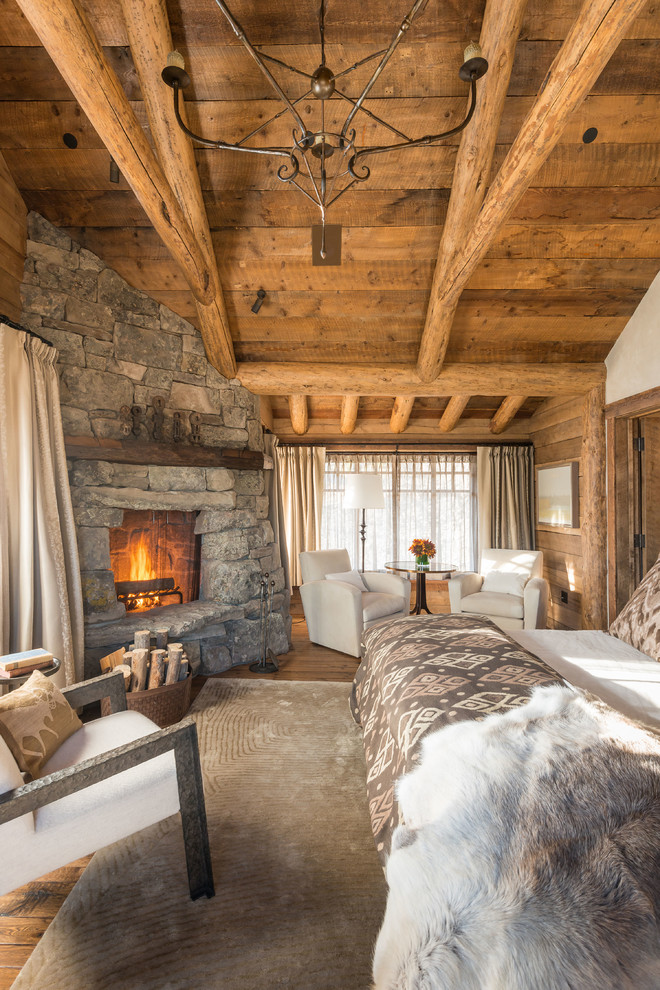 A fireplace clad with natural stone is one of the best features you could have in a rustic bedroom. Just make sure you have one or two comfy chairs near by.